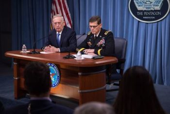 Two men sitting at a table in front of reporters