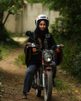 Habiba Suleiman Sefu on her motorbike, in her role as Malaria hunter (USAID)