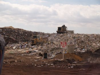 A bulldozer moving trash around a landfill