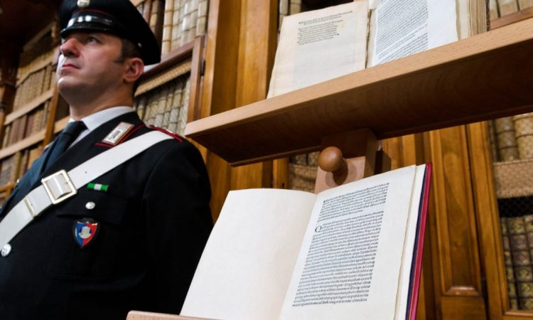 A Carabinieri police officer stands next to a copy of a 1493 letter by Christopher Columbus about the discovery of the New World. (© AP Images)