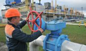 Man wearing hard hat turning a valve on a pipeline