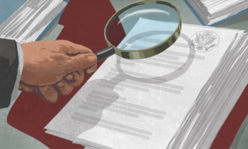 Hand holding a magnifying glass over a stack of documents