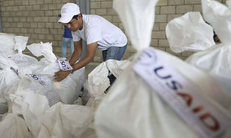 A Venezuelan volunteer places a bag of USAID humanitarian aid for storage at a warehouse next to the Tienditas International Bridge, near Cucuta, Colombia, on the border with Venezuela.
