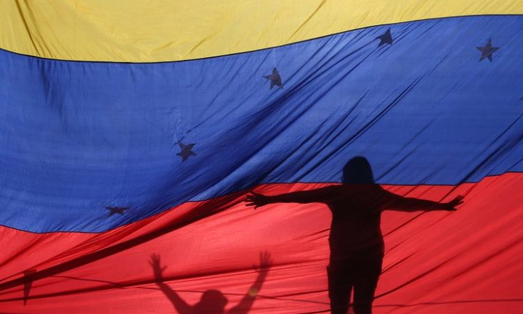 Silhouettes behind a flag of Venezuela